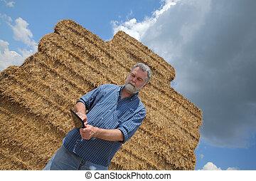 Farmer inspecting bale of straw in field