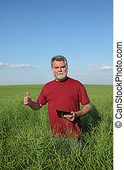 Farmer inspecting rapeseed crop in field and gesturing