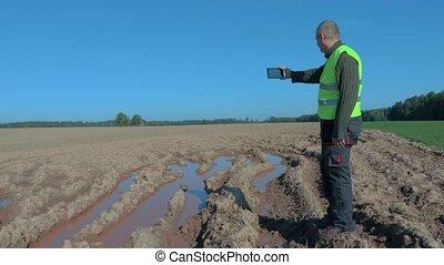 Farmer inspecting the wet field