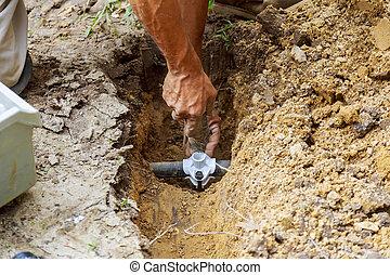 farmer installing irrigation system