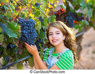 Farmer kid girl in vineyard harvest autumn leaves in Mediterranean