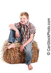 farmer kid sitting on hay