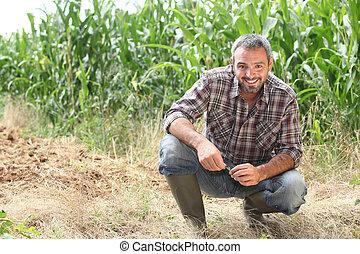 Farmer kneeling by crops