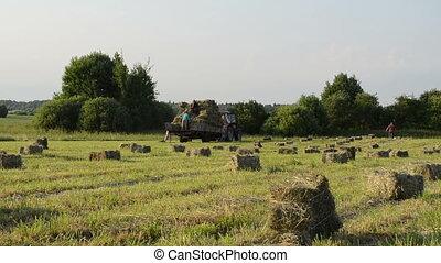farmer load hay bale
