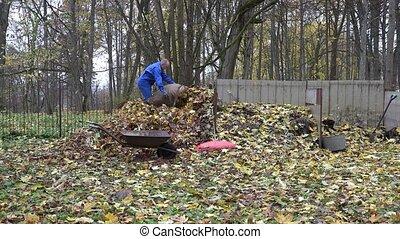 Farmer man carry barrow bag sack full of leaves and dump it on compost pile. 4K