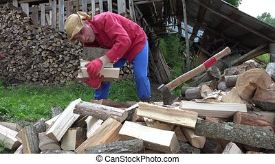 Farmer man pick chopped firewood in truss and stack near woodshed. Static shot. 4K