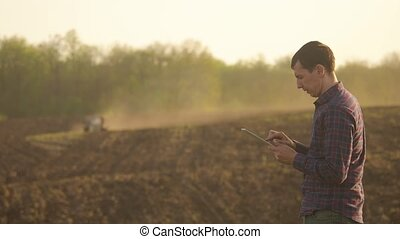 Farmer man read or analysis a report in tablet computer on a...