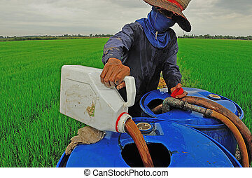 farmer mixing pesticide on the rice field