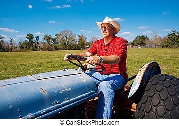Handsome mature farmer on his tractor, mowing the field.