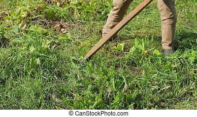 Farmer mows the grass on his stead. Physical work. Hard...