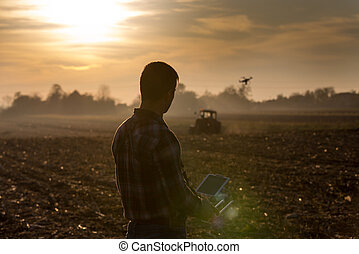 Farmer navigating drone above farmland
