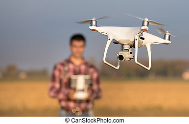 Farmer navigating drone above farmland - Close up of flying...