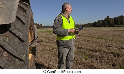 Farmer near tractor with tablet pc