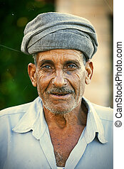 Old man posing outdoor wearing a traditional turban