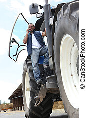 Farmer on a tractor using a mobile phone