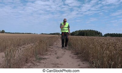 Farmer on cereal field with walkie talkie