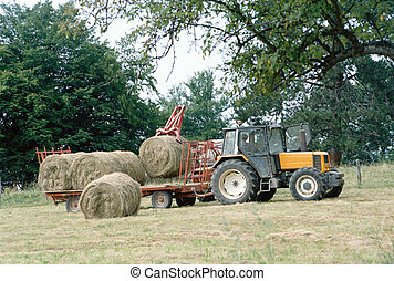Farmer on his tractor picking up haystacks in Savoy, France...