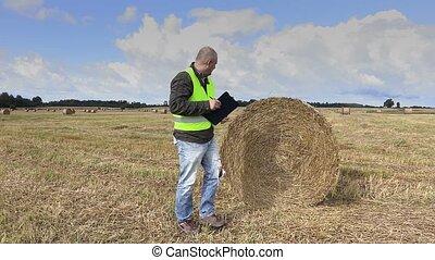 Farmer on the field near straw bale