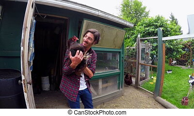 Farmer playing with hen in hen house 4k - Male farmer...