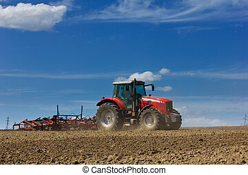 Farmer plowing the field. Cultivating tractor in the field. ...