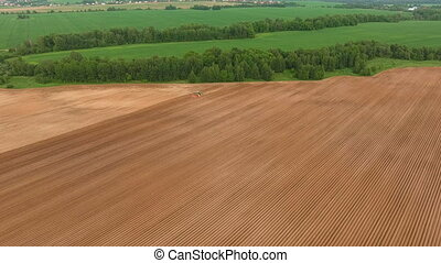 Farmer seeding, sowing crops at field.Aerial view. - Aerial...