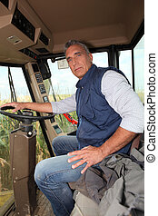 Farmer sitting in the cab of a combine harvester
