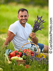 Farmer sitting in the grass with a basket of vegetables