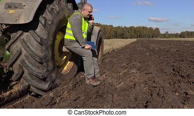 Farmer sitting near tractor wheel and talking on phone