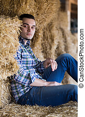 farmer sitting on haystack at shed