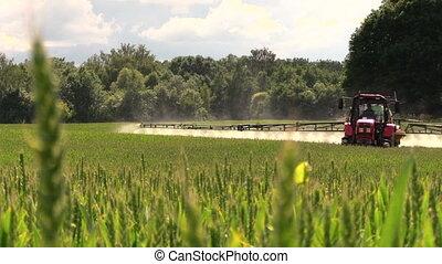 farmer spray field - Farmer with tractor spray fertilize...
