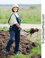 farmer spreads manure - Female farmer spreads manure at farm...