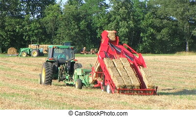 Farmer Square Baling Hay - Farmer operating hay baler and...