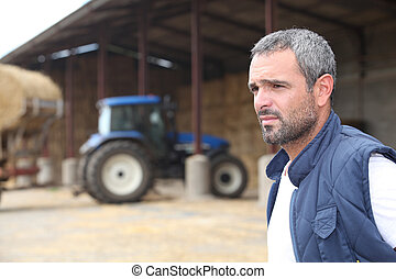 Farmer standing in front of a barn containing a tractor