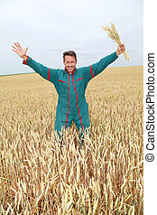 Farmer standing in wheat field with arms up