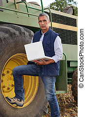 Farmer standing next to his large John Deere tractor with a ...