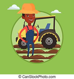 Farmer standing with tractor on background. -...