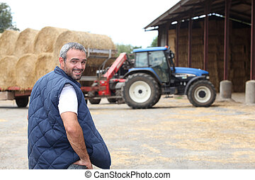 Farmer stood by hay barn