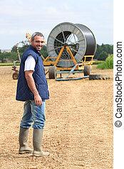 Farmer stood in field machinery in background
