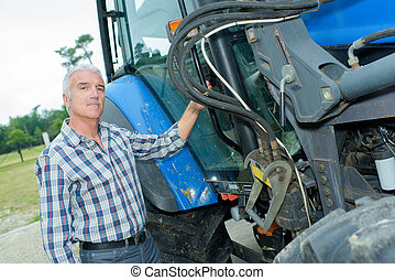 Farmer stood next to tractor