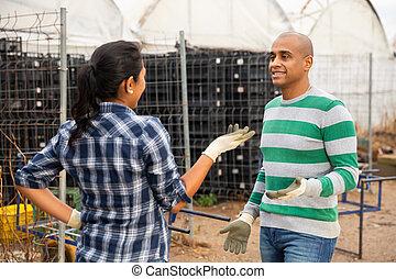 Farmer talking to female partner in farm yard