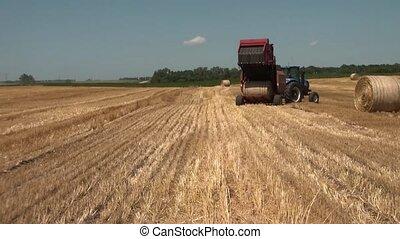 Farmer Unloads Hay Bail