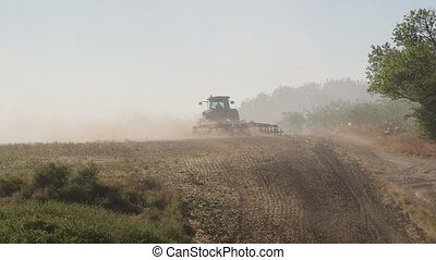Farmer using modern farm tractor with disk harrows for...