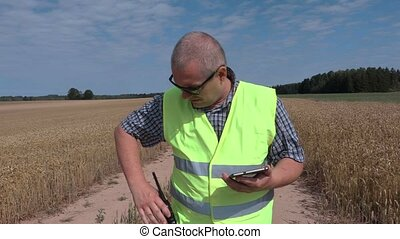 Farmer using tablet and walkie talkie on cereal field