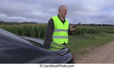 Farmer using walkie talkie near corn field