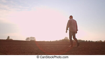 Farmer walking in idyllic,rural plowed field at sunset. Farmer wiping off sweat from forehead while walking on the field at sunset. Rubber boots for work use. A worker go with rubber boots at sunset.