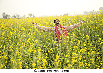 Farmer with arms outstretched in rapeseed field