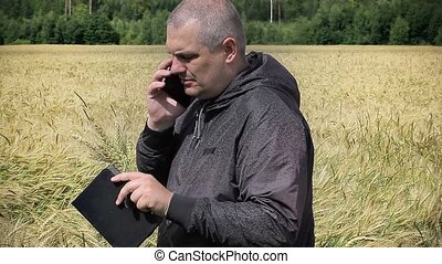 Farmer with cell phone near yellow cereal field