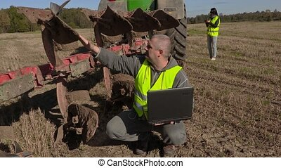 Farmer with computer at the plow
