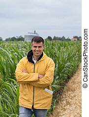 Farmer with crossed arms in corn field