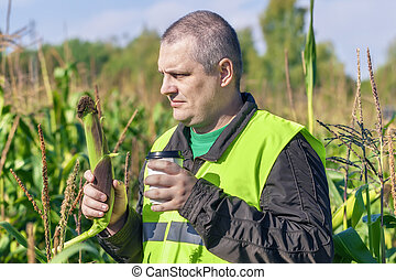 Farmer with cup of coffee and corn